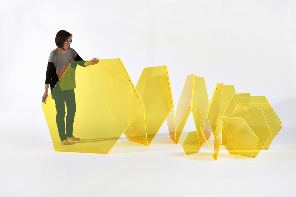 "Marta Chilindrón, ""Hex Spiral"" (alternate view with artist), 2013, Fluorescent yellow plexi, plastic hinges and screws, 48 x 110 x 90 in. Photo credit: Arturo Sanchez."